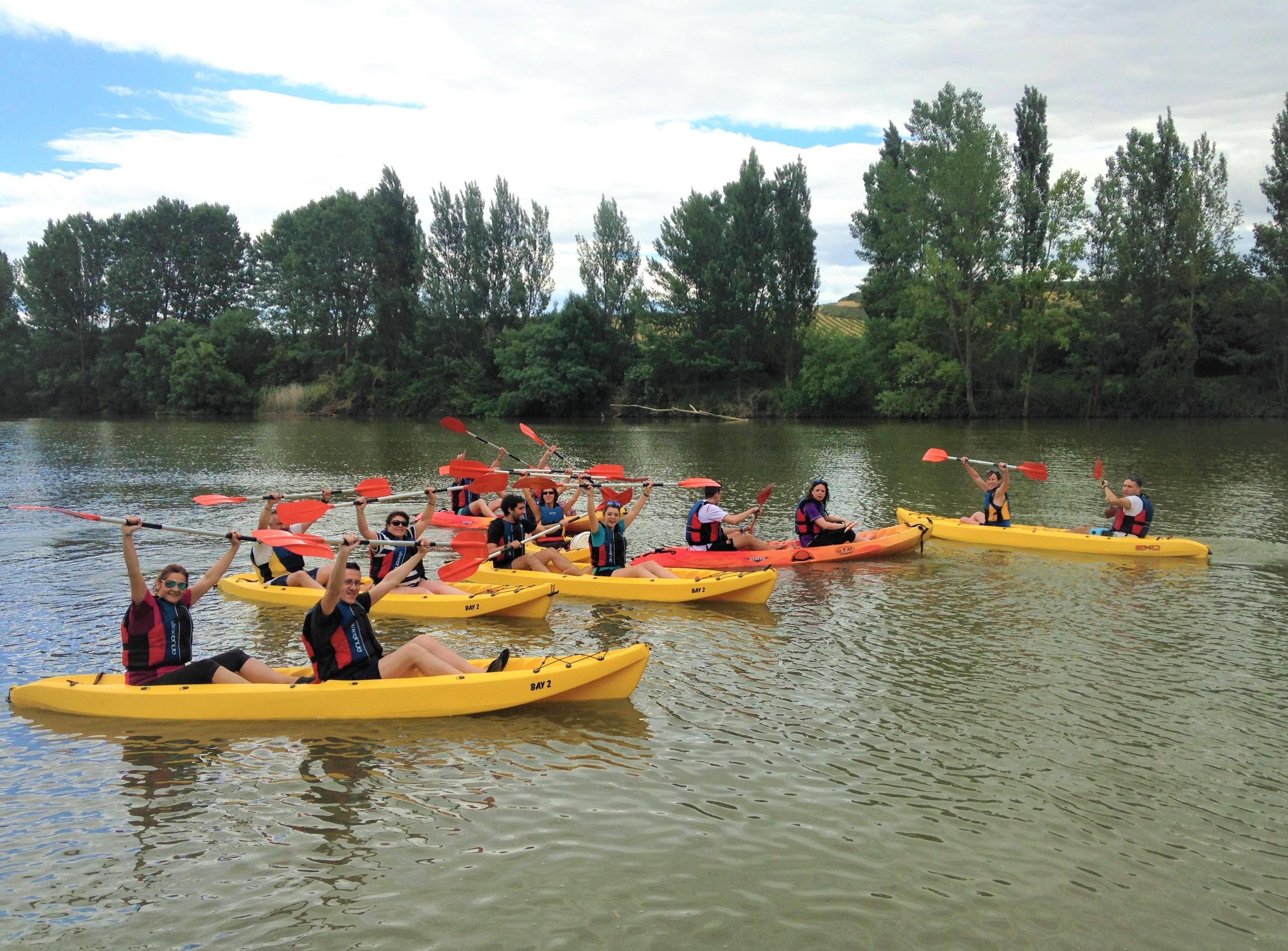 un grupo de unas 20 personas disfrutando de un paseo en kayak por el rio ebro montados en caoas amarillas y levantando los brazos en forma de alegría